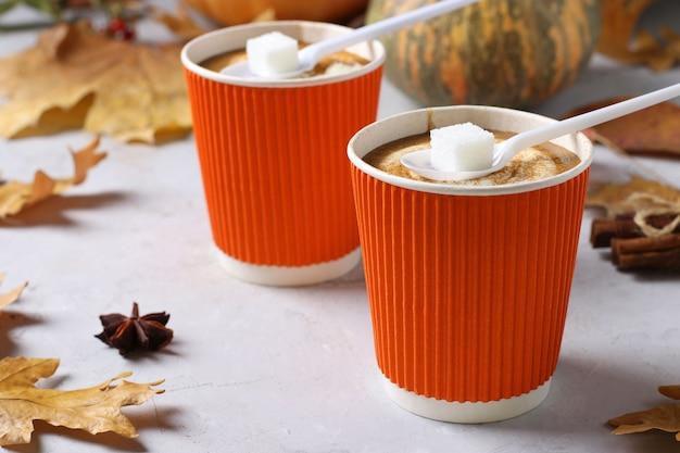 Pappbecher mit leckerem kürbis latte und gewürzen auf grauem tisch. nahansicht. horizontalformat.