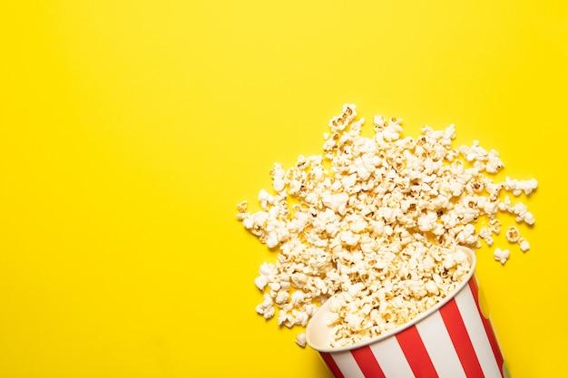 Pappbecher mit popcorn auf gelbem grund, platz für text.