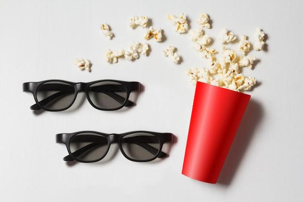 Pappbecher mit verstreutem popcorn und gläsern auf weiß