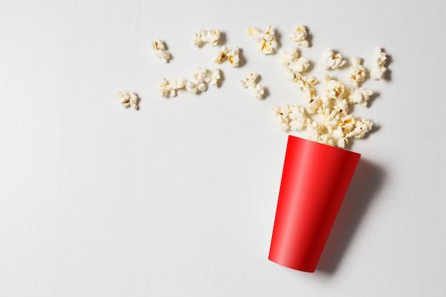 Pappbecher mit verstreutem popcorn weiß