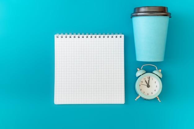 Pappbecher und uhr mit einem notizbuch mit auf einem blauen hintergrund