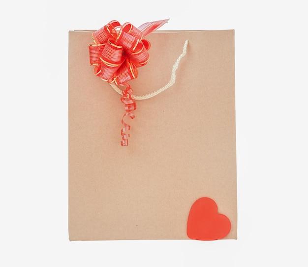 Pappbeutel isolieren. einweg-öko-tasche mit roter schleife und rotem herzen auf weißem hintergrund