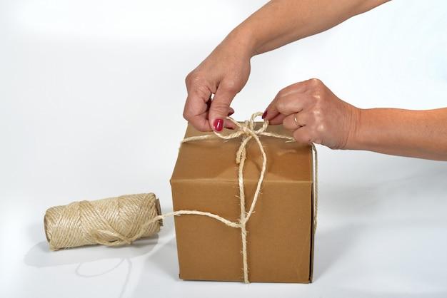 Pappe, die eine junge frau mit einer schnurspule verpackt