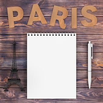 Pappe paris-schild mit eiffelturm, stift und leerem notizbuch mit freiem platz für ihr design über holztisch extreme nahaufnahme. 3d-rendering