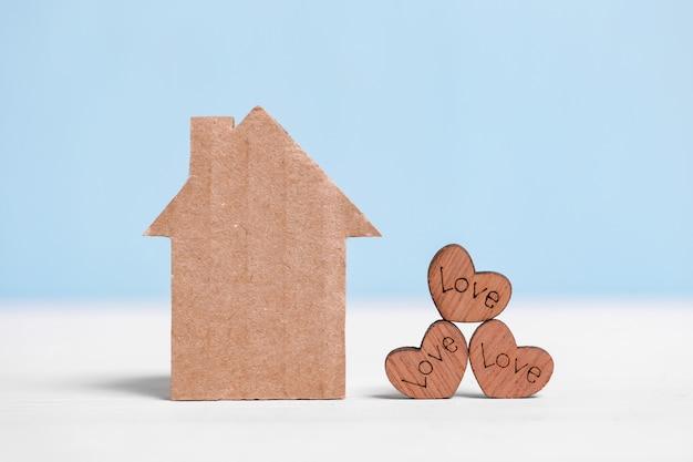 Papphaus und hölzerne herzen mit aufschriften lieben auf blau und weiß.