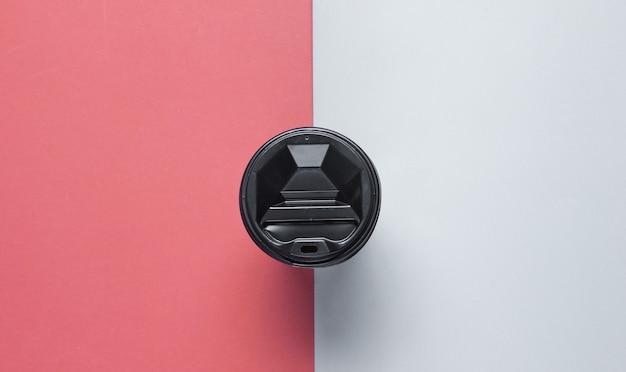 Pappkaffeebehälter mit deckel auf grau-rotem hintergrund. draufsicht