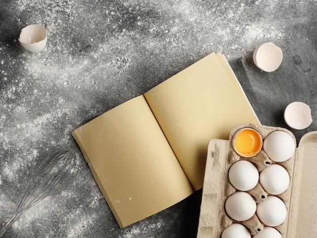 Pappkarton mit weißen hühnereiern, bastelpapierrezeptbuch auf grauem tisch. von oben betrachten.
