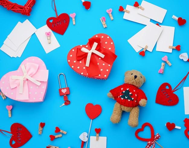 Pappkartons in form eines herzens, ein kleiner teddybär, weiße leere visitenkarten mit wäscheklammern