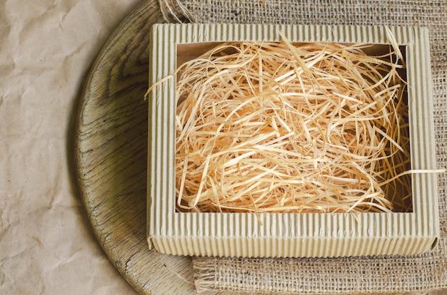 Pappschachtel gefüllt mit trockenem gelbem stroh auf einer holzkiste, einem leinwandstoff und einem packpapier, getont und verblasst