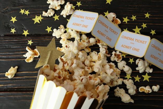 Pappschachtel mit popcorn und tickets auf holzhintergrund.