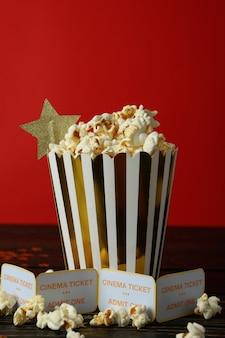 Pappschachtel mit popcorn und tickets vor rotem hintergrund.