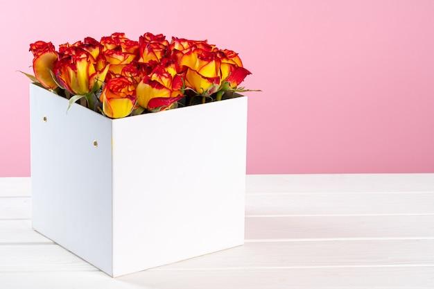 Pappschachtel mit rosen auf rosa hintergrund