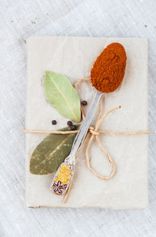 Paprika auf dem löffel, dem lorbeerblatt und einem notizbuch für rezept