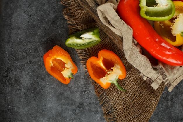 Paprika auf einem steintisch auf einem stück sackleinen. draufsicht.
