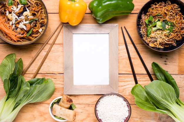 Paprika; bokchoy; hackstock; frühlingsrollen; schüssel mit reis und udon-nudeln auf schreibtisch aus holz