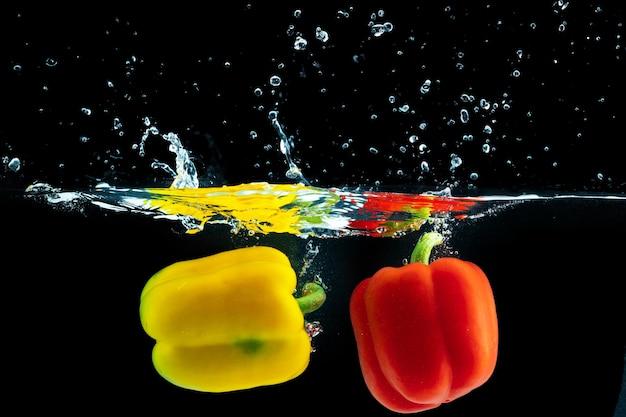 Paprika fällt mit einem spritzer gegen schwarz ins wasser