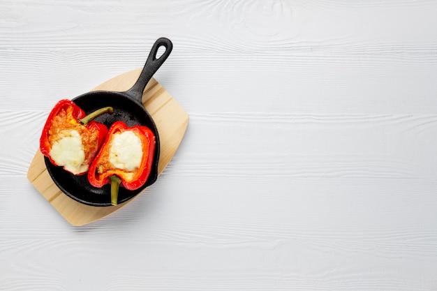Paprika gefüllt mit fleisch mit geschmolzenem käse mozzarella oben im ofen in gusseisen pfanne gebacken