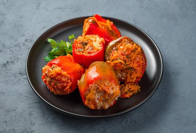 Paprika gefüllt mit putenfleischreis und gemüse in einem schwarzen teller auf dunkelgraublauem hintergrund