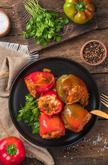 Paprika gefüllt mit putenreis und gemüse auf braunem hintergrund mit frischen kräutern