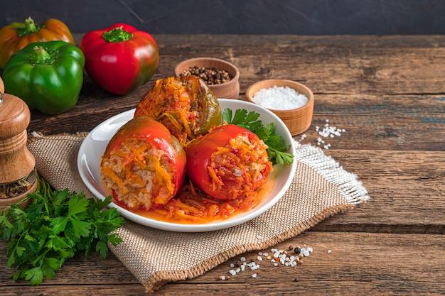 Paprika gefüllt mit putenreis und gemüse auf braunem holzhintergrund