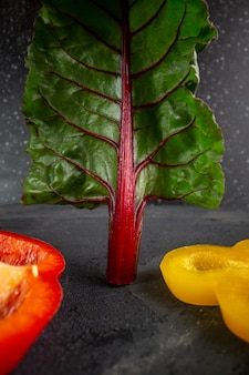 Paprika geschnittene reife rote und gelbe paprika zusammen mit grünem blatt auf grauem hintergrund