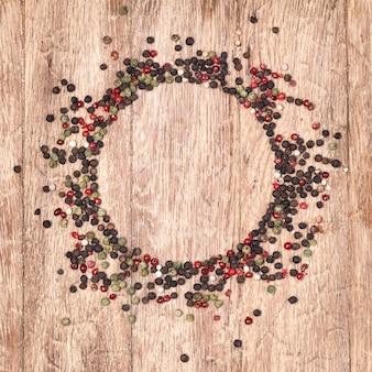 Paprika heißer, roter, schwarzer, weißer und grüner pfeffer auf hölzernem hintergrund.