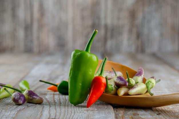 Paprika in einem holzlöffel auf einem holz.