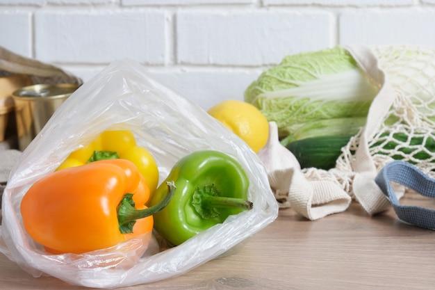 Paprika in einer plastiktüte auf einem hölzernen küchentisch