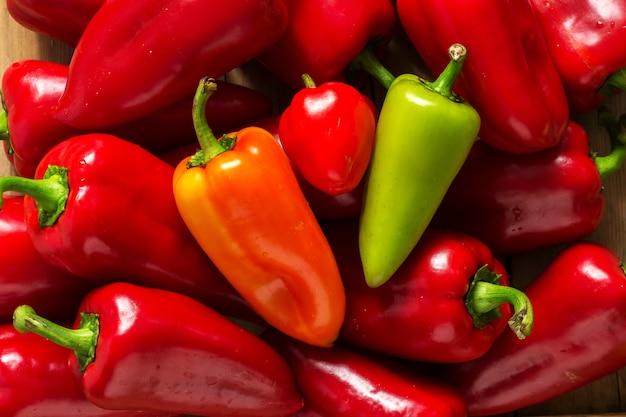 Paprika in verschiedenen farben auf einer holzoberfläche. selektiver fokus.