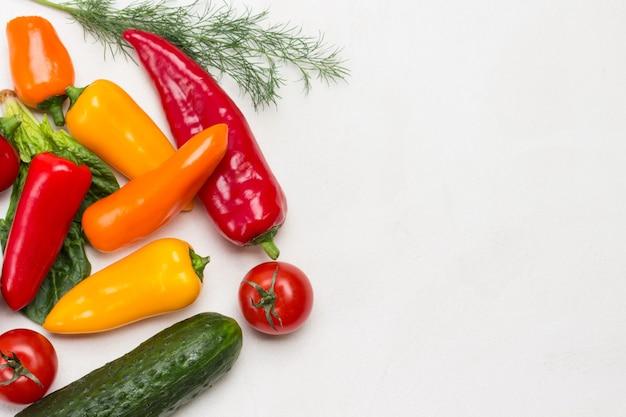 Paprika in verschiedenen farben, gurken und tomaten. weißer hintergrund. flach liegen. platz kopieren