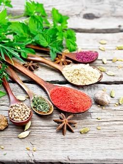 Paprika, ingwer, koriander, getrockneter thymian und sumach in löffeln, muskatnuss, kardamom, sternanis und bockshornklee