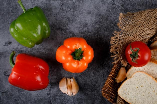 Paprika, knoblauch und tomaten mit brotscheiben.