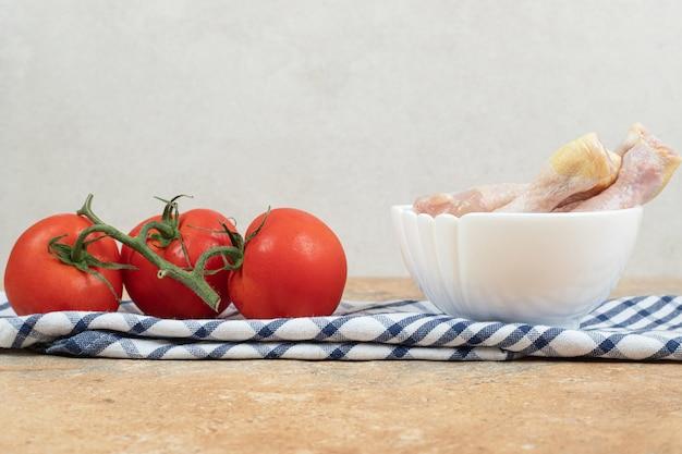 Paprika mit rohen hähnchenschenkeln auf tischdecke
