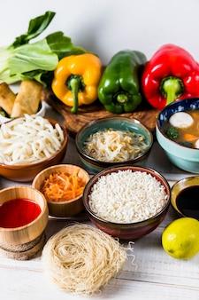 Paprika; sprießen bohnen; reis; udon-nudeln; saucen und trockene reissuppennudeln auf weißem schreibtisch
