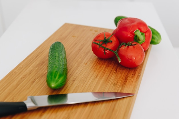 Paprika, tomaten, gurken auf einem schneidebrett mit einem messer