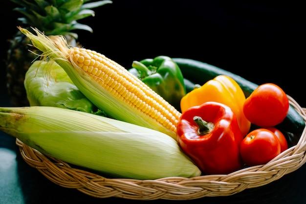 Paprika, tomaten, mais, gurken und salat aus frischem gemüse in einen korb legen