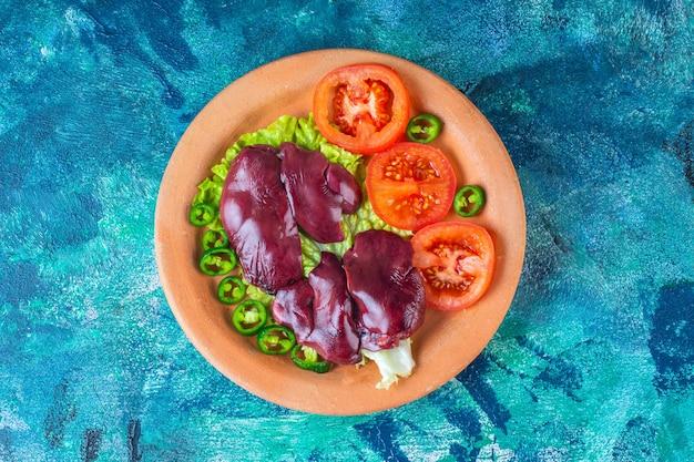 Paprika, tomaten, salat und hühnerinnereien auf einem tonteller