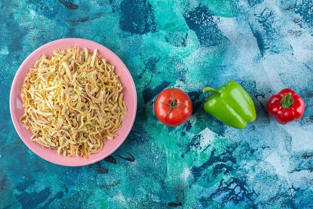 Paprika, tomaten und nudeln in einem teller auf dem blauen tisch.