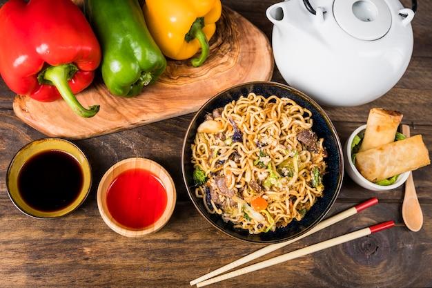 Paprika; udon-nudeln; saucen und frühlingsrollen auf weißem schreibtisch