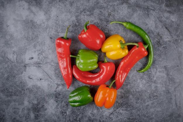Paprika und chilis in gemischten farben in der mitte des hintergrunds. draufsicht.