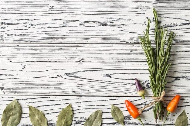 Paprika- und rosmarinzweige mit lorbeerblättern auf hölzernem
