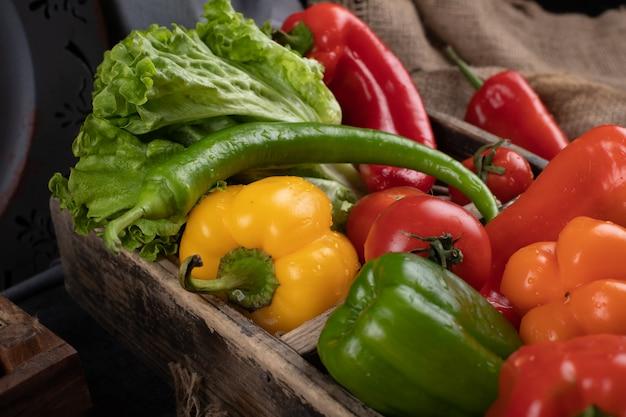 Paprika und salat in einem holztablett.