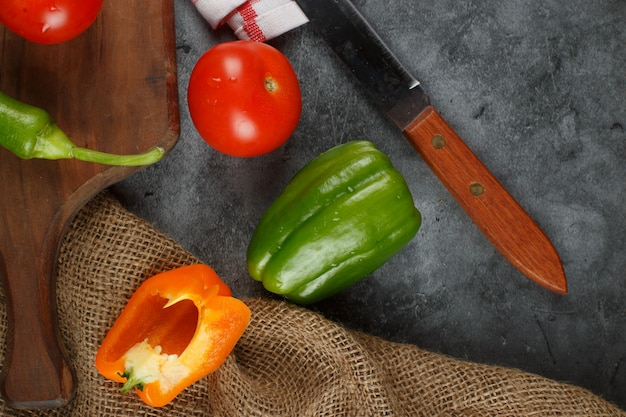 Paprika und tomaten auf einem steintisch mit einem messer. draufsicht.