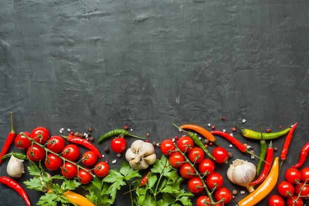 Paprikakirschtomatenknoblauch und andere gewürze auf schwarzem