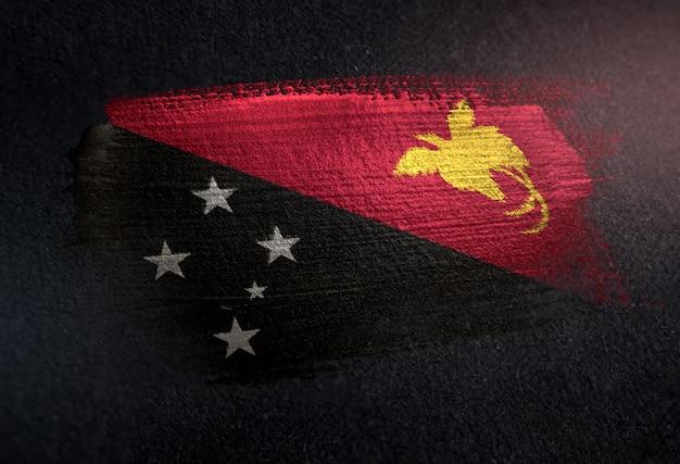 Papua-neu-guinea-flagge gemacht von der metallischen bürsten-farbe auf dunkler wand des schmutzes