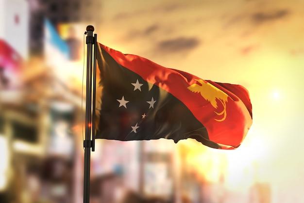 Papua-neuguinea-flagge gegen stadt verschwommener hintergrund bei sonnenaufgang-hintergrundbeleuchtung