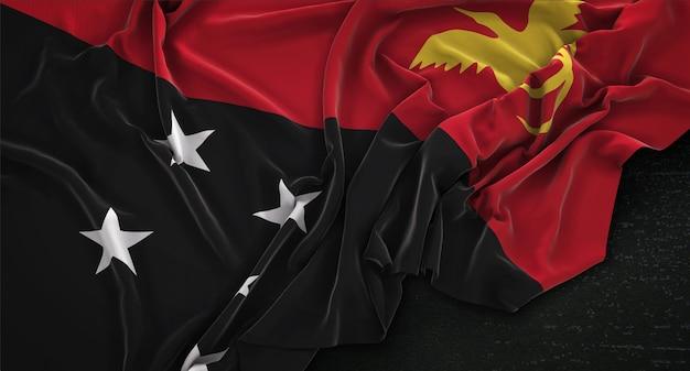 Papua-neuguinea-flagge geknickt auf dunklem hintergrund 3d-render