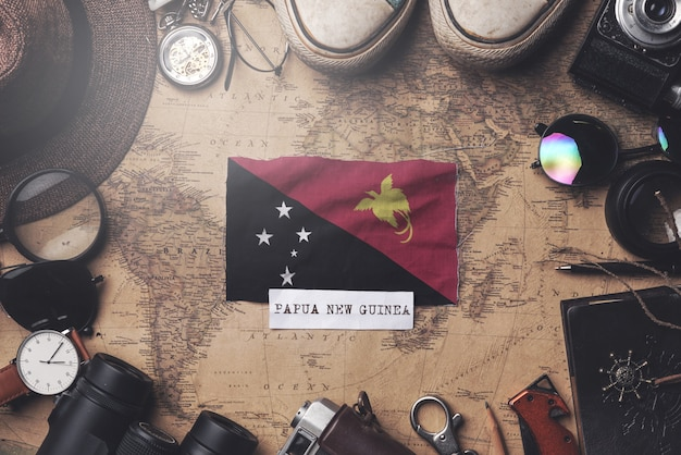 Papua-neuguinea-flagge zwischen dem zubehör des reisenden auf alter weinlese-karte. obenliegender schuss