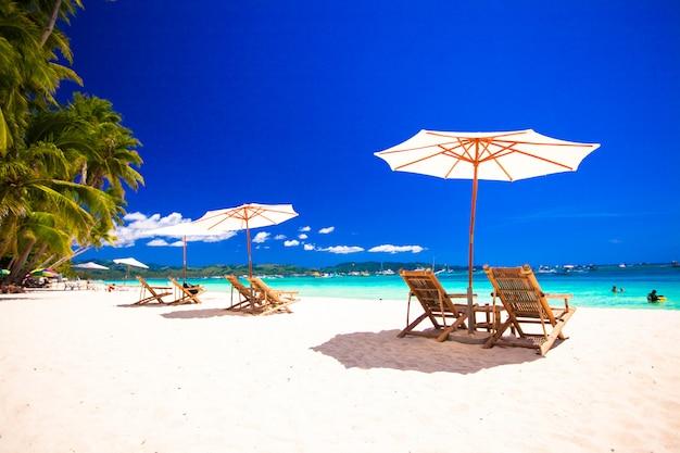 Paradiesansicht des netten tropischen leeren sandigen strandes mit regenschirm und strandstuhl