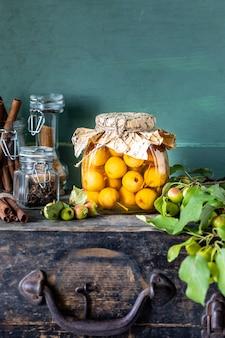 Paradiesapfelmarmelade und paradiesäpfel in zuckersirup auf einer alten holzoberfläche